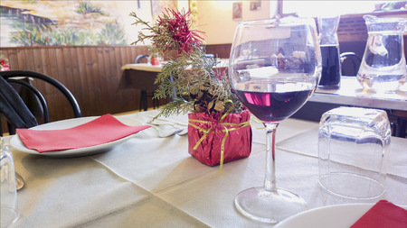 table with white skateryu in restaurant. Wine glasses and Cutlery on table.
