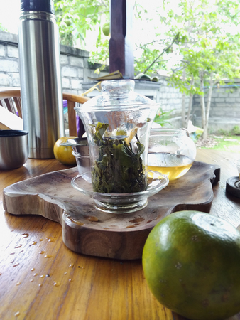 Green and black tea ceremony. Glass teapot for aroma therapy and relaxation. Wooden tray. Tea tree leaves.