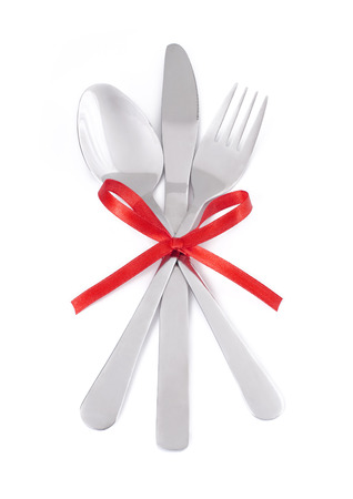 Crossed fork, knife and spoon on white background with red ribbon.  photo