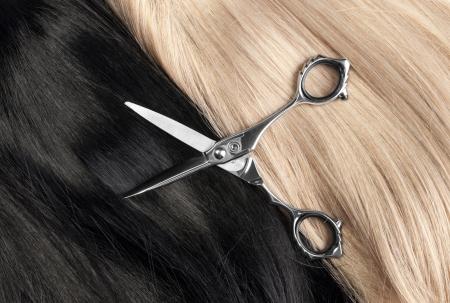 cabello rubio: Cortar un cabello negro y rubio largo y liso Foto de archivo
