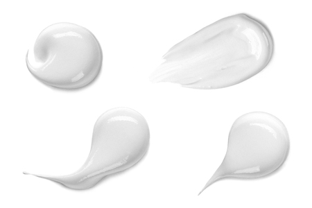 Collection of various strokes of a white beauty cream on white background