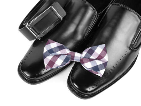 Close up of black male shoes, bow tie and belt on white background