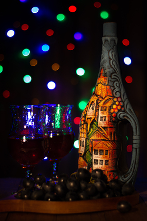 Festive bottle on a dark background with bright lights, with grape wine in the glasses and a bunch of grapes in the foreground. Banco de Imagens