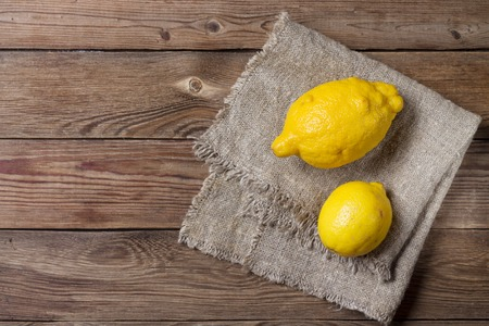 Two trendy ugly organic lemons on a natural wooden background, on napkin. Horizontal orientation of the image. Copy space