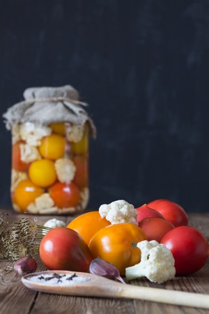Preparation of fermented vegetables. Fresh tomatoes,cauliflower,spices in the foreground. Dark background. Copy space Banco de Imagens
