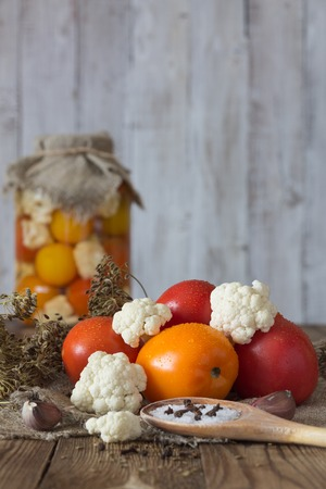 Preparation of fermented vegetables. Fresh tomatoes,cauliflower,spices in the foreground. Natural white background