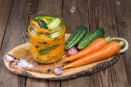 Traditional Korean snack of cucumbers in a glass jar: cucumbers marinated with carrots, hot pepper and garlic, with vegetable oil, on a wooden stand.