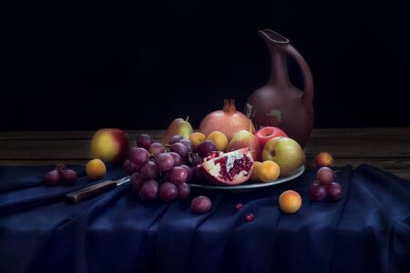 Still life with a jug of wine and fruit on a plate (pomegranate, red grapes, apples and pears, apricots) on a dark blue linen tablecloth on a black background. Horizontal orientation.
