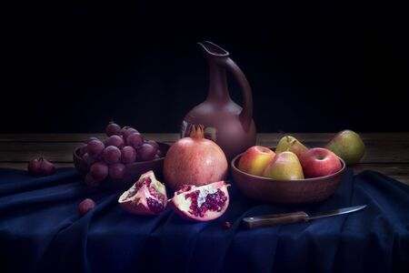 Still life with a jug of wine, pomegranate, red grapes, apples and pears on a dark blue linen tablecloth on a black background. The image has a horizontal orientation. Copy space Stok Fotoğraf