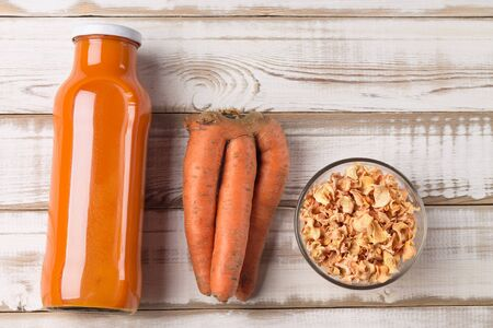 Ugly carrots, dried chips and natural carrot juice in a bottle, on a light wooden background. The image shows how you can use non- standard vegetables.