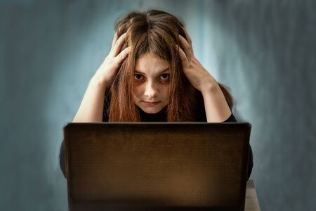 A girl sits at a computer and holds her head in her hands. She has a sickly look and disheveled hair after a long sitting at the computer. Selective focus. Stock fotó