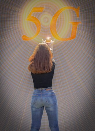 A young girl stands with her back and holds out her hands with a telephone. At the top, the inscription 5G lights up and rays emanate from it. Selective focus