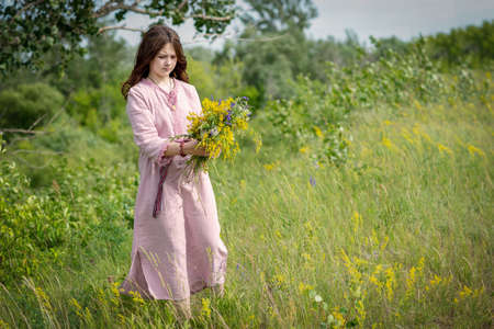 A young Russian girl collects a bouquet of wildflowers at the Kupala holiday.
