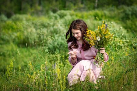 A young Russian girl collects flowers on a summer meadow for a wreath at the Kupala holiday.