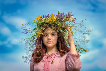 A young Russian girl spreads a wreath of wildflowers on her head. At the Kupala holiday.
