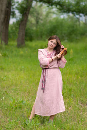 A young Russian girl in a traditional Slavic costume is combing her hair with a wooden comb. I bathed the holiday.