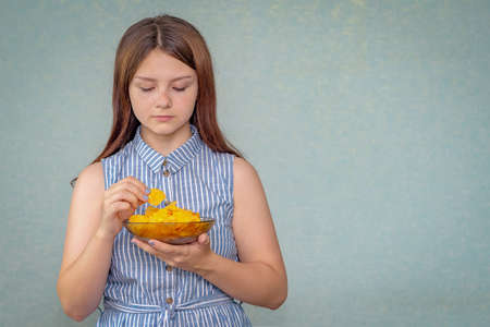 A young girl holds a plate of chips in her hand