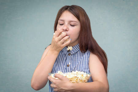 A young girl holds a glass bowl of popcorn in her hand and eats this fast food with pleasure.