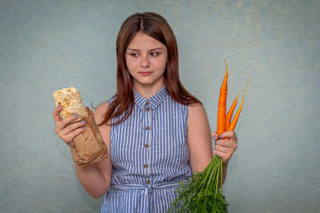 A young girl holds fresh carrots in one hand and shawarma in the other Stock fotó