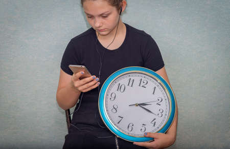 A girl with headphones sits, holds a large wall clock in one hand, a mobile phone in the other and looks at a gadget. Time is wasted for a teenager Stock fotó