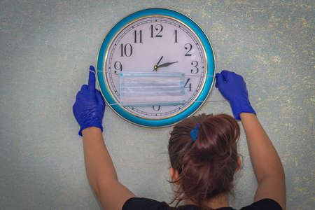 There is a clock on the wall. A girl in medical gloves brings a medical mask to the clock, protecting time from the virus