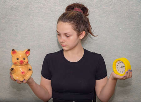 A young girl holds a watch in one hand and a piggy bank in the other, looks at the piggy bank and ponders the choice time or money