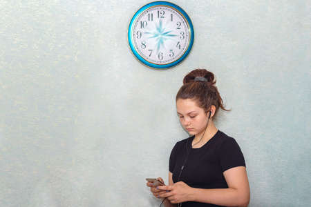 A young girl in headphones stands under the clock and looks at a mobile phone. On the wall clock, the hands seemed to have frozen in motion, time has stopped for the teenager Stock fotó