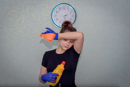 A young girl is standing in the room, the clock is on the wall. The girl holds a napkin and a plastic bottle in her hands. She was cleaning up, tired, and wiping the sweat from her forehead