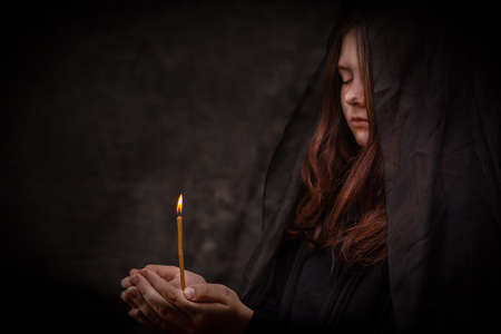 The girl in black holds a burning church candle in her hands.