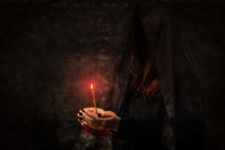 Black girl without a face with a burning candle in her hands.