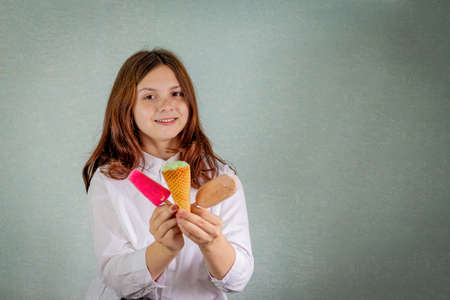 A young girl holds chocolate, pistachio and fruit ice cream Stock fotó