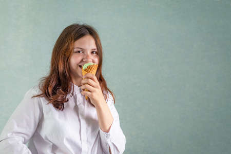 A young girl bites a pistachio ice cream in a waffle cup Stock fotó