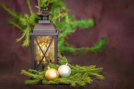 New Year. Ancient lantern, with fir branches, next to two Christmas tree toys in gold and silver colors