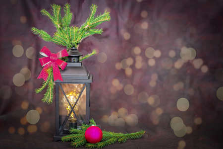Ancient lantern, with fir branches and a festive bow, next to a Christmas tree toy purple