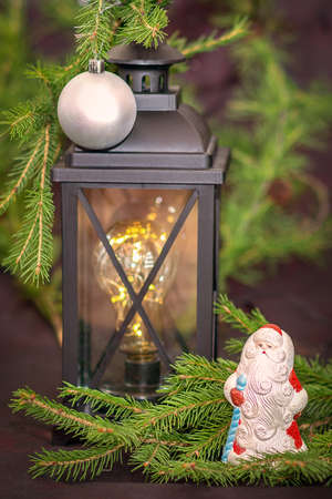 New Year. Ancient lantern, with fir branches, on it a silver ball, next to the figure of Santa Claus Stock fotó