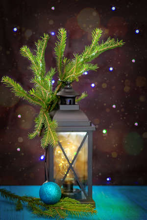 New Year. Ancient lantern, with fir branches, next to the Christmas tree toy blue