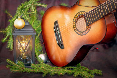 New Year's Eve. Old lantern, two Christmas toys, a guitar on spruce twigs. Selective trick