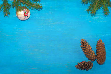 At the top of the branches were spruce with a Christmas tree toy. At the bottom there are three fir cones. Blue background. Horizontal position