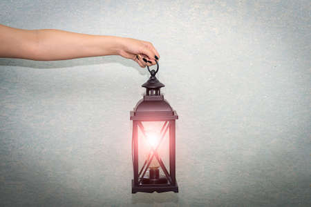 The hand holds the antique lamp, the lamp illuminates the space. Stock fotó