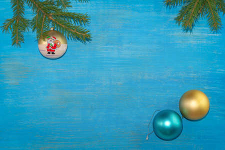 At the top of the branches were spruce with a Christmas tree toy. At the bottom there are two balls of gold and turquoise color. Blue background. Horizontal position