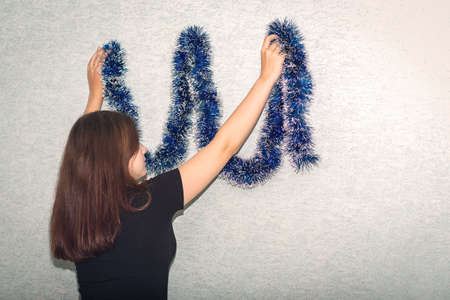 The girl decorates the wall with a blue tinsel Stock fotó