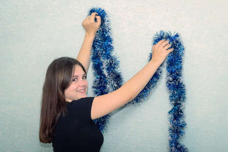 The girl decorates the wall with a blue tinsel, turns around and smiles