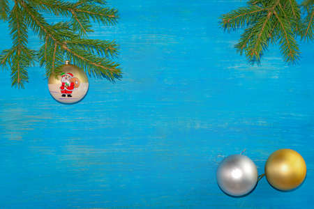 At the top of the branches were spruce with a Christmas tree toy. At the bottom there are two balls of gold and silver color. Blue background. Horizontal position
