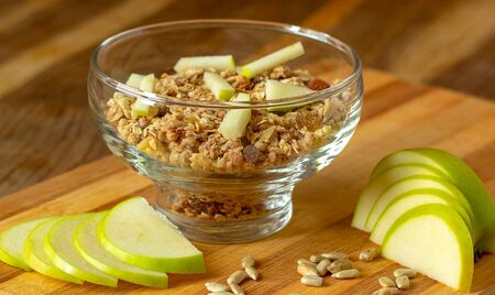 Oatmeal in a glass bowl, next to it is a sliced apple. Selective focus