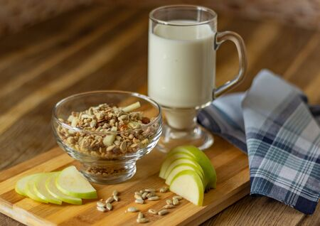 Oatmeal in a glass bowl, next to a mug of milk and lies a chopped apple. Selective focus, place for text Zdjęcie Seryjne