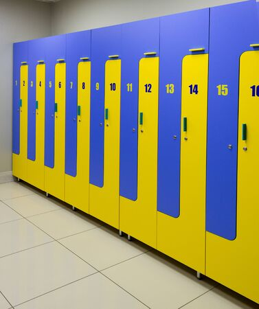classic locker room with blue and yellow rows of lockers. 免版税图像