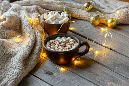 Mug with cocoa and marshmallows, sweater, decorated with LEDs. Winter mood. Cozy winter composition.