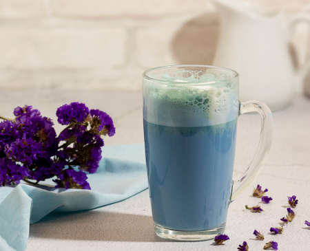 Blue matcha tea in a glass of latte on the table. Place for text. Horizontal orientation. Selective focus