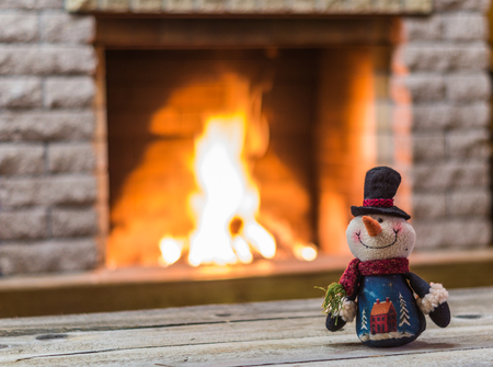 toy  snowman  aginst  the  background of  the fireplace. Stock Photo