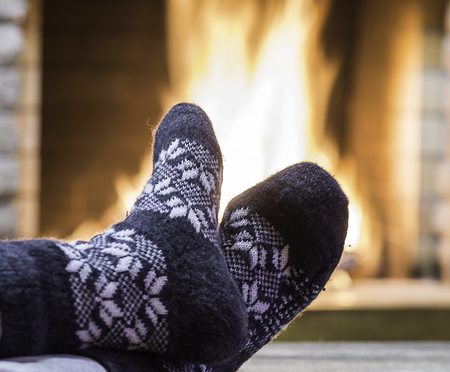 Mans Feet in lovely gray socks, before the fireplace, in the country house. Stock Photo